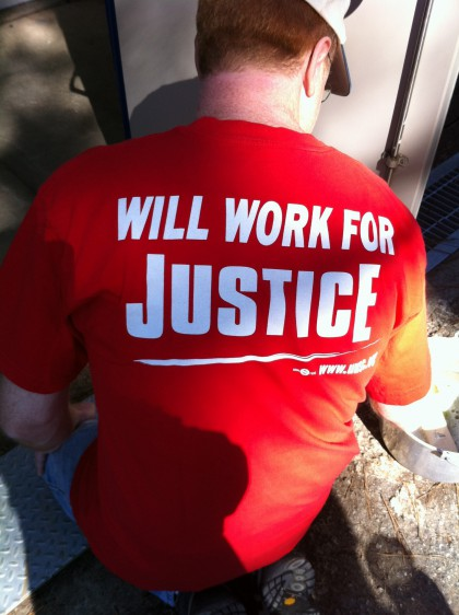"Helping hand's T-Shirt reads ""Will work for Justice"""